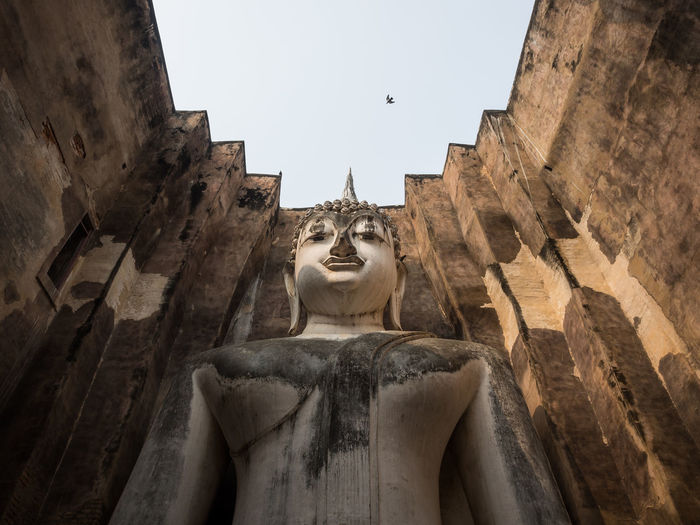 Low Angle View Of Buddha Statue On Building Against Sky
