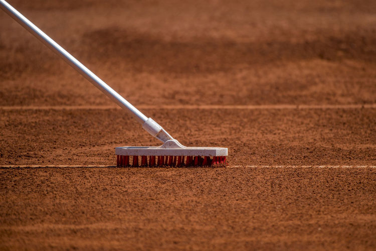 Worker cleans a line of tennis court with a brush Cleaning Tennis Tennis Ball Tennis Player Work Working Action Active Active Lifestyle  Brown Brush Clean Cleaning Cleansing Close-up Court Day Dirt Golf Land Leisure Activity Motion Nature No People Outdoors Playing Field Proper Property Sand Selective Focus Sport Sports Still Life Sun Sunset Tennis Tennis Court Tennis Net Tennis 🎾 Tenniscourt