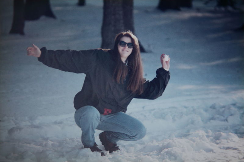 Woman kneeling on snow in forest