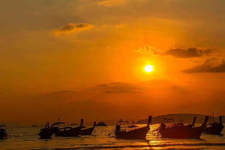 Silhouette boats moored in sea against orange sky