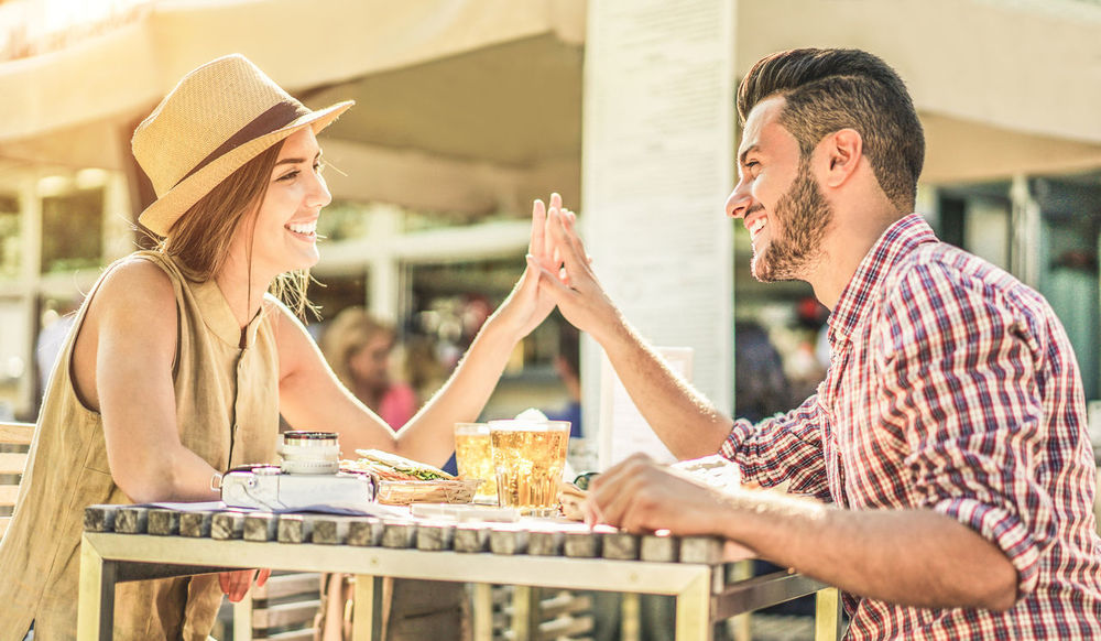 Couple in love during travel vacation Date Dinner Hands Happy Hollidays Love Lover Meal Moment Travel Young Boyfriend Girlfriend Happiness Holding Location Outdoors People Reataurant Smiling Summer Sun Table Tender Togetherness
