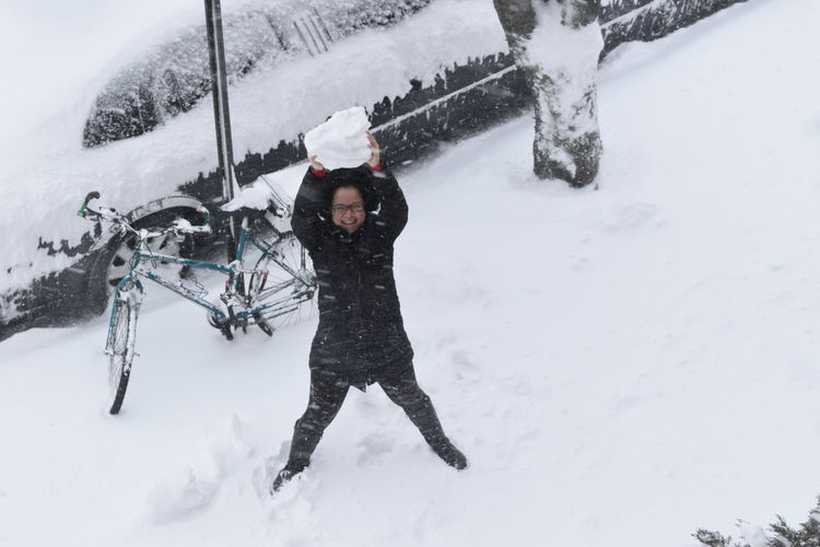 Happy Woman With Snowball Standing On Hill During Snowfall