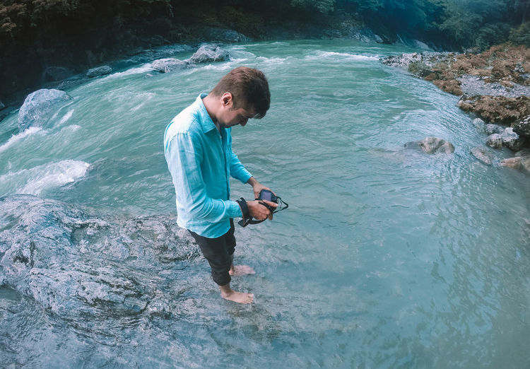 Full length of man photographing while standing in river