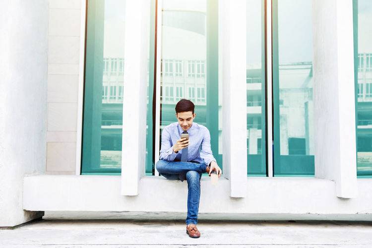 Businessman Using Mobile Phone While Sitting Against Building