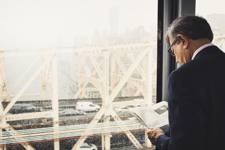 Business man. Back View Business Cloudy Man Reading Traffic Transportation Adult Businessman City Indoors  Lifestyles Newspaper One Person Rainy Window