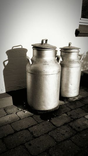 High angle view of milk canisters against wall