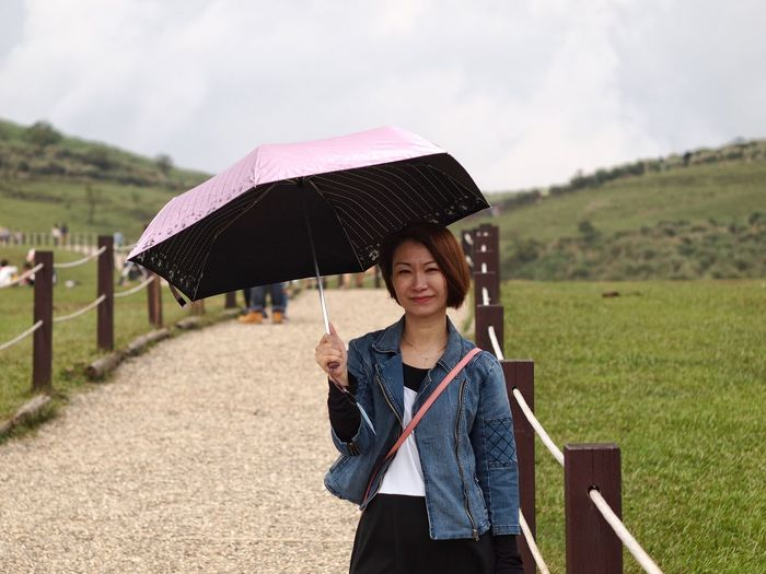 Portrait of young woman with umbrella in rain