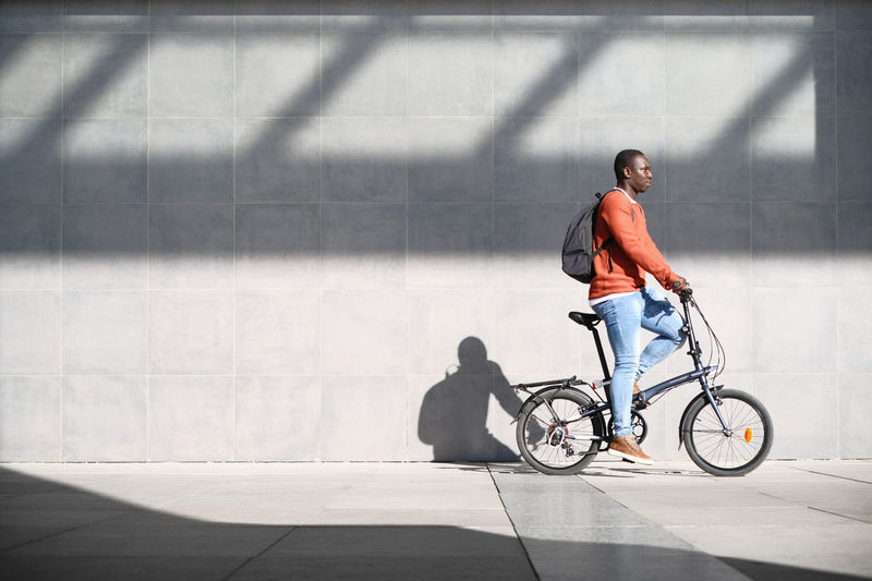 Full length of man cycling against wall