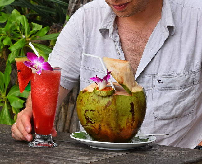 Midsection of man with drink and coconut on wooden table