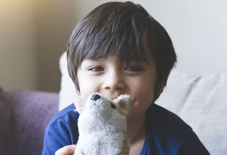 Portrait of cute boy holding stuffed toy at home