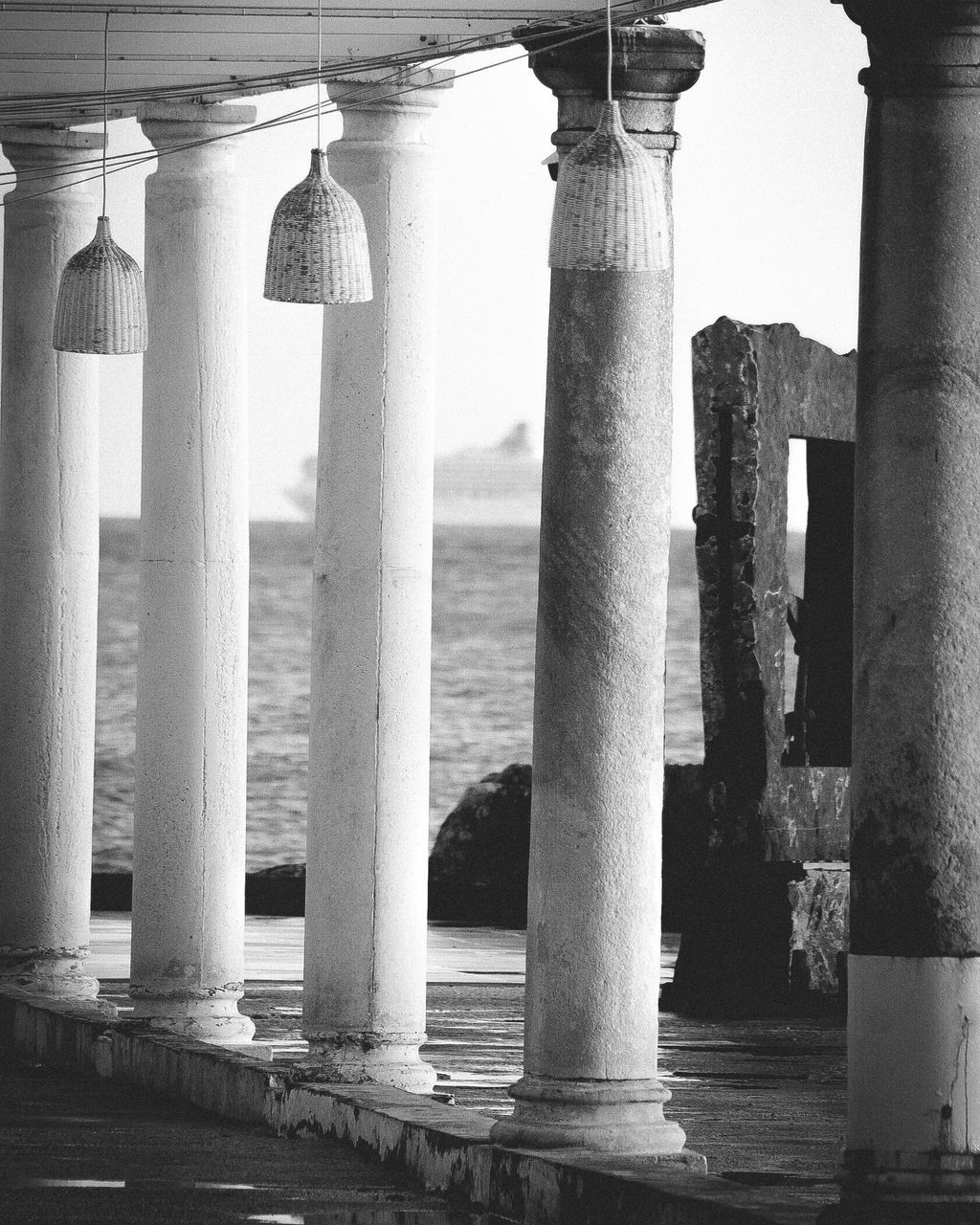 architectural column, architecture, built structure, water, colonnade, in a row, no people, day, building, the past, history, building exterior, outdoors, nature, travel destinations, connection, strength, arcade, sea, balustrade