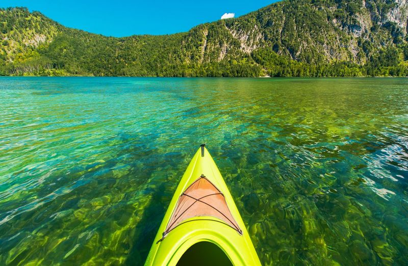 Scenic Turquoise Lake Kayaking. Almsee in the Austria, Europe. Sports and Recreation Theme. Austria Sportsman Almsee Beauty In Nature Day Floating On Water Kayak Land Mountain Nature Nautical Vessel No People Outdoors Plant Scenics - Nature Sea Sky Tranquil Scene Tranquility Transportation Travel Destinations Trip Turquoise Colored Water
