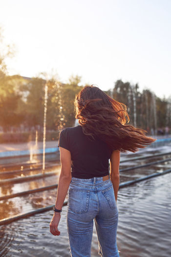 Beautiful young woman with flying hair at sunset time