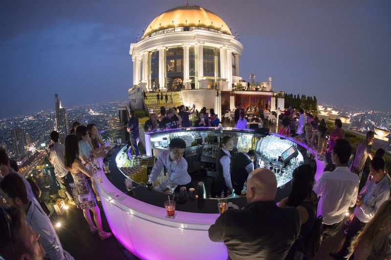 Crowd enjoying party on terrace at night against sky