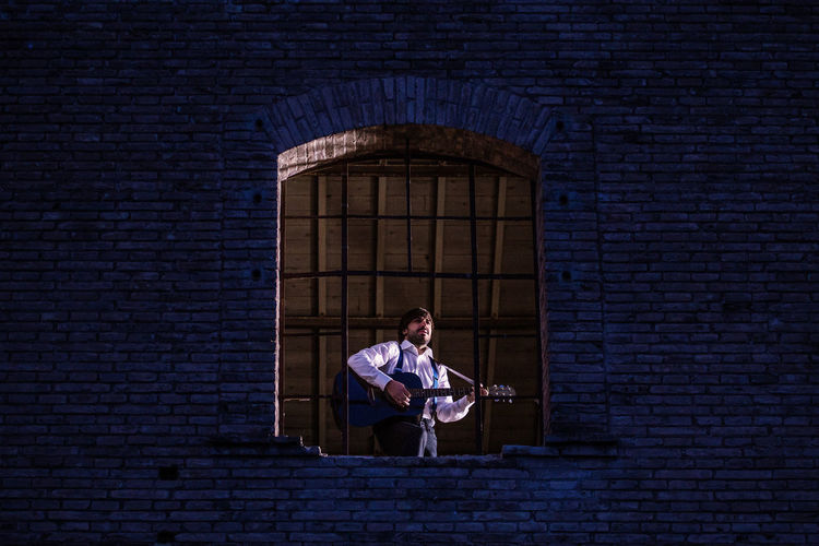 Low Angle View Of Man Playing Guitar While Standing At Window