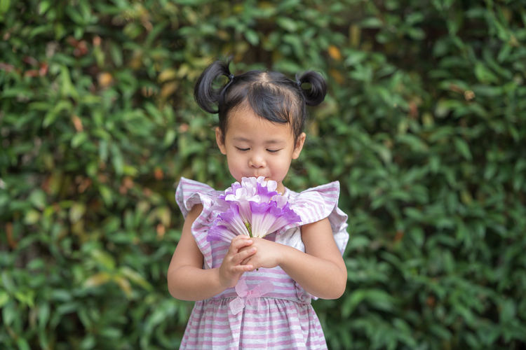 Girl smelling bunch of flowers while standing outdoors