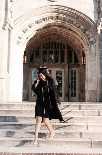 Full Length Of Young Woman In Graduation Gown Moving Down On Steps Against College