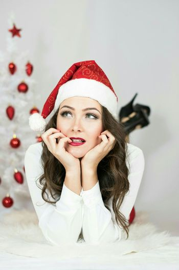 Thoughtful Woman Wearing Santa Hat Lying On Bed