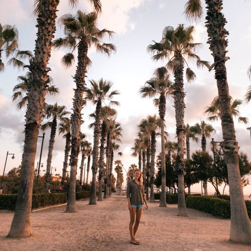 Full length portrait of woman standing on sand against trees