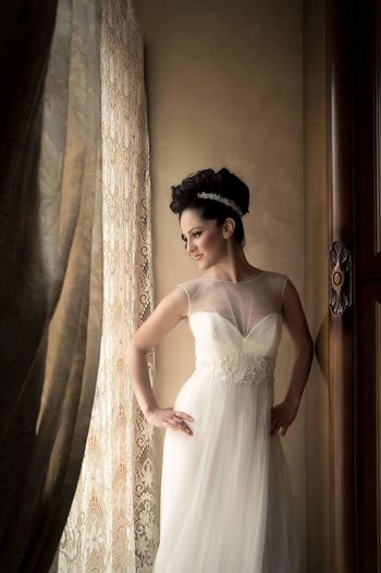 Bride with hands on hip standing by window
