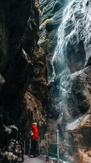 Man walking on rock by waterfall