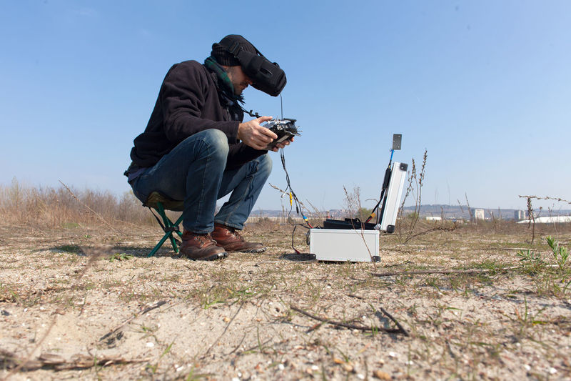 Man Operating Drone With Remote Control While Sitting On Field Against Sky