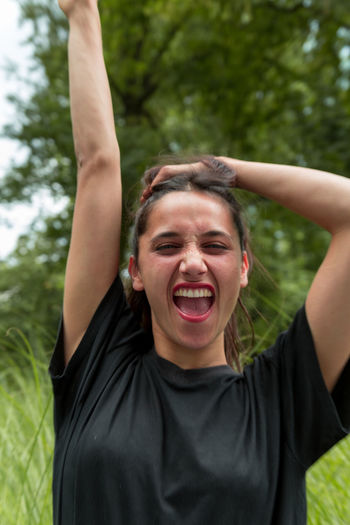 Young woman screaming with arm raised high. Arms Raised Front View One Person Happiness Cheerful Mouth Open Real People Positive Emotion Shouting Excitement Portrait Indian Ethnicity Medium Close Up One Woman Only Beautiful Woman Mixed Race Person
