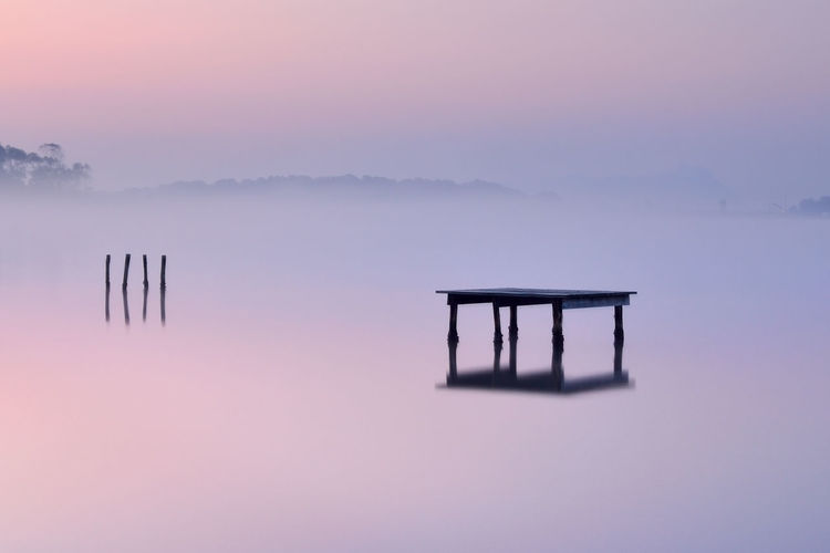 Silhouette wooden posts in lake against sky during sunset