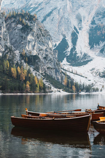 Boats moored on lake against snow covered mountain