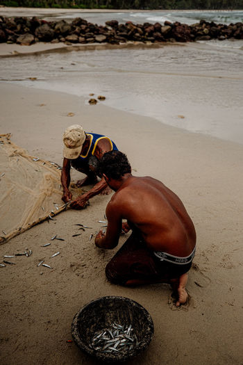 Beach Land Sand Day Real People People Full Length Shirtless Sea Nature Men Water High Angle View Outdoors Leisure Activity Bending Lifestyles Crouching Fisherman