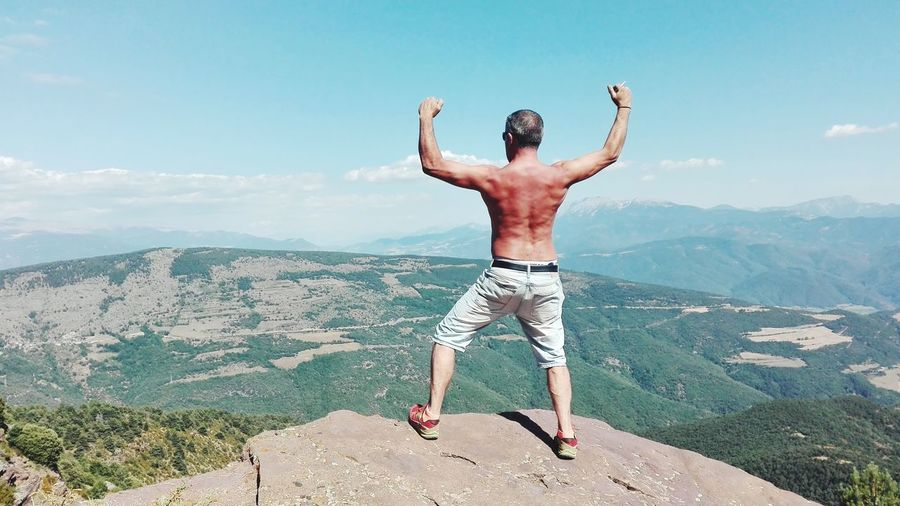 Rear view of shirtless man flexing muscles while standing on cliff against sky