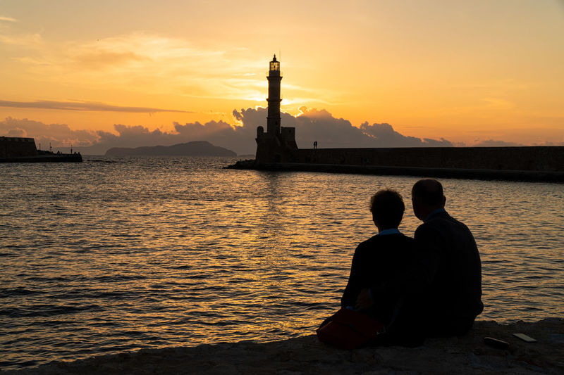 Silhouette people sitting on shore against orange sunset sky