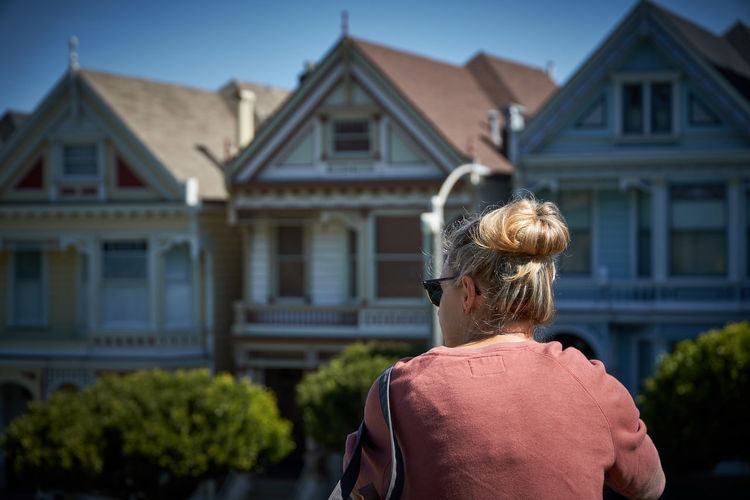 Rear view of woman standing outside house
