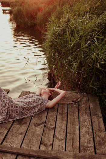 Low section of woman sitting on wooden bench