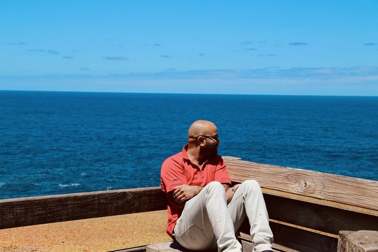 Man sitting on bench by sea against sky
