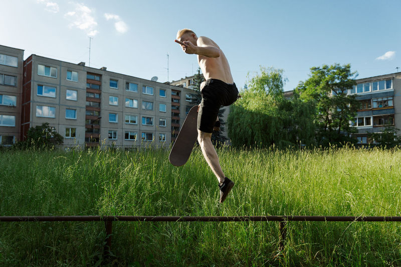 Full length of man showing obscene gesture while jumping over plant