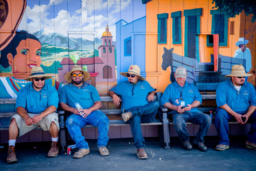 Hispanic workers taking a lunch break together in front of a mural Architecture Blue Wave Bonding Boys Building Exterior Casual Clothing Friendship Front View Hispanic Leisure Activity Lifestyles Looking At Camera Men Mexican Mid Adult Multi Colored Outdoors Person Portrait Rest Resting Taking A Break Togetherness Traditional Clothing Workers