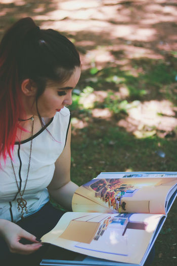Woman looking at pictures on book while crouching at park