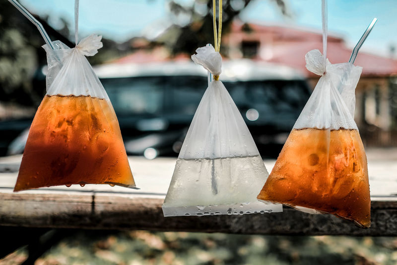 Close-up of drink in plastic bags hanging for sale
