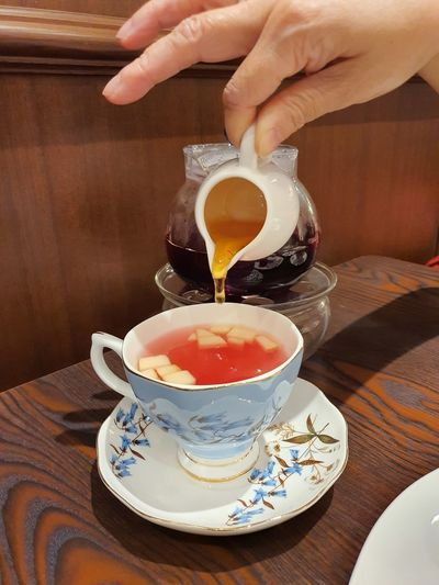 Midsection of person pouring tea cup on table