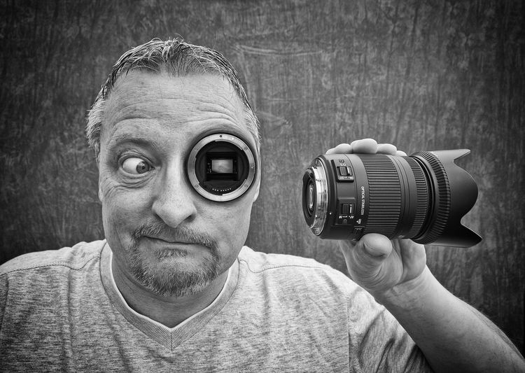 Digital composite image of mature man with photographic eye holding camera lens