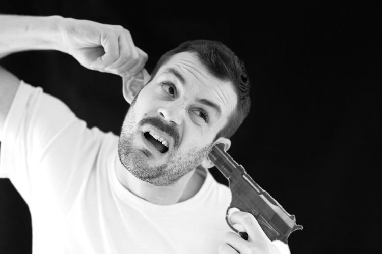 Man pointing gun in ear against black background