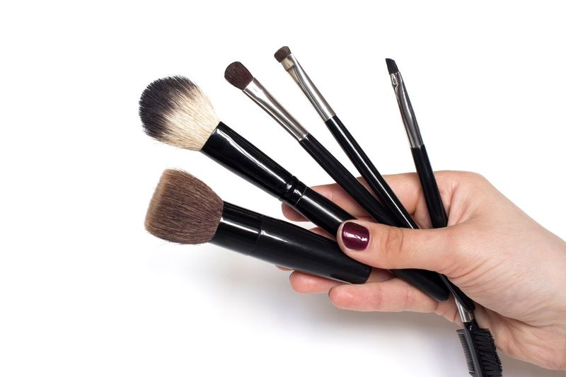 Young woman holding makeup brushes in her hand Fashion Beauty Product Brushes Makeupartist Cosmetics White Background Copy Space Close-up Studio Shot White Background Nail Creativity Holding Make-up Brush Cut Out Women