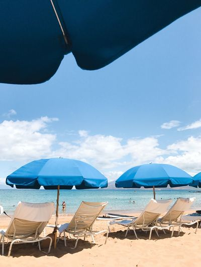 Empty Lounge Chairs By Blue Parasols At Sandy Beach