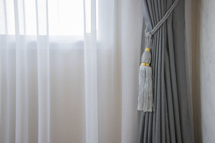Close-up of curtain tied on window at home