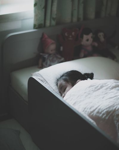 High Angle View Of Girl Sleeping On Bed At Home