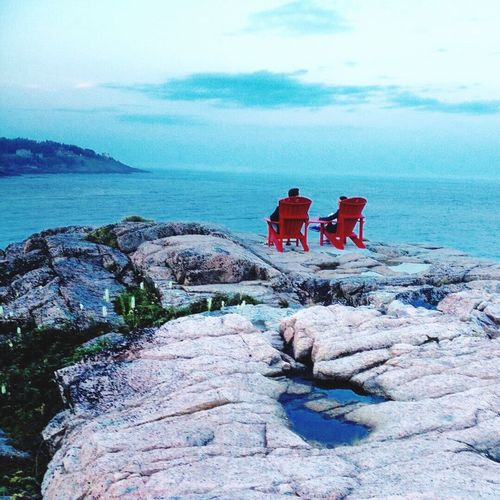 Friends sitting on adirondack chairs at rock formation by sea against sky