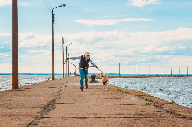 Man with dog on beach against sky