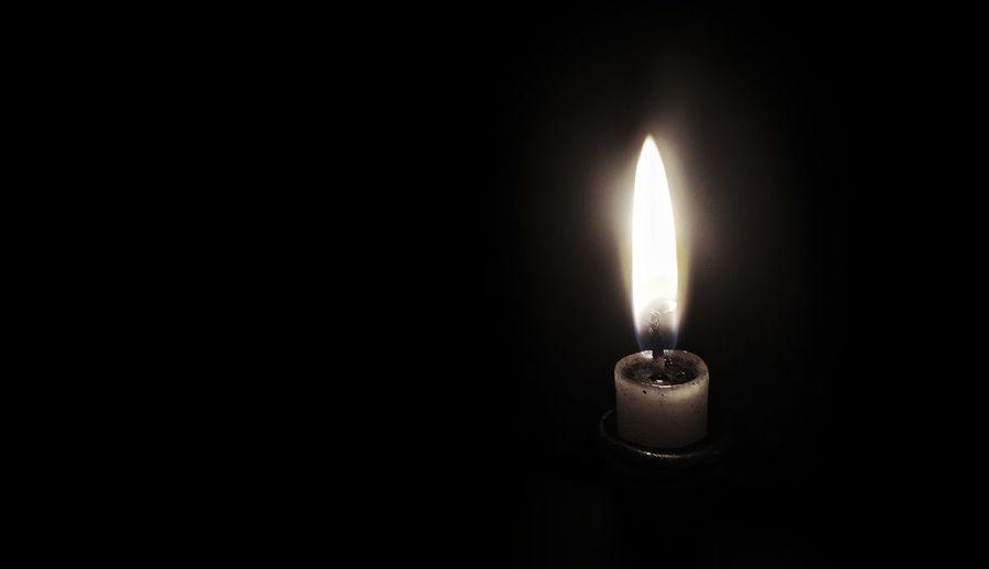 Close-up of illuminated candle in darkroom
