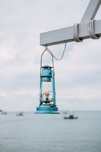 Close-up of lantern hanging against sky